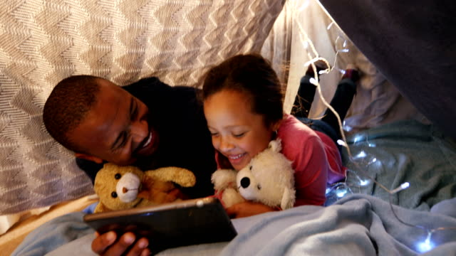 Father and daughter using digital tablet in bedroom 4k