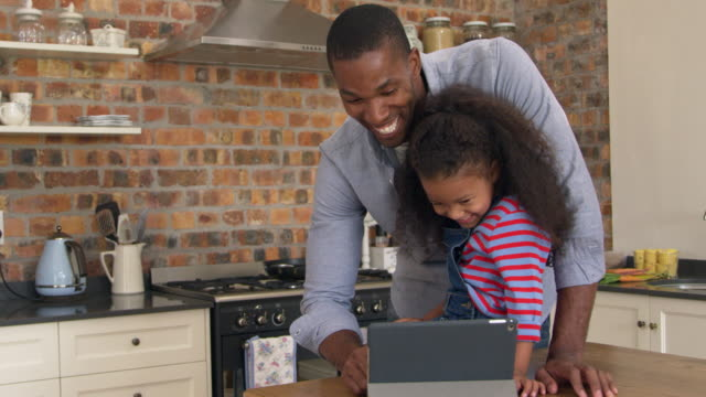 Father And Daughter Using Digital Tablet In Kitchen At Home video