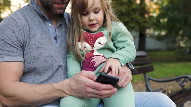 Father and daughter using smartphone on bench in autumn park