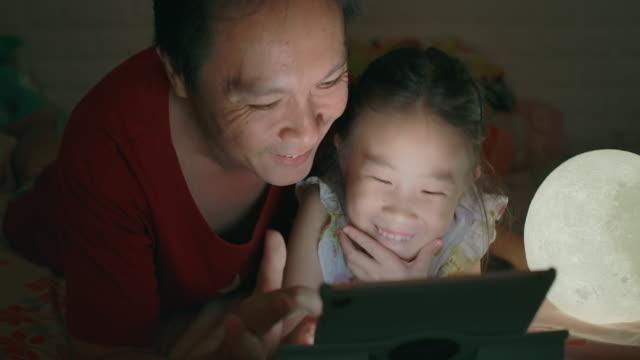 far och dotter använder tablet i sovrummet - digital reading child bildbanksvideor och videomaterial från bakom kulisserna