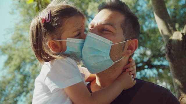 far och dotter som bär skyddsmasker i parken under coronavirusepidemin. far håller och omfamnar sin dotter. skott i slow motion - krama bildbanksvideor och videomaterial från bakom kulisserna