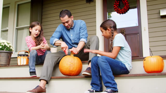 father and daughters carving halloween pumpkin on house steps - autumn stock videos and b-roll footage