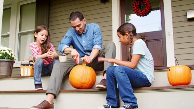 vídeos de stock, filmes e b-roll de pai e filhas esculpir a abóbora de halloween na casa passos - outono