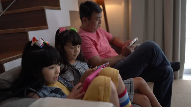 Father and daughters using electronic device at home video