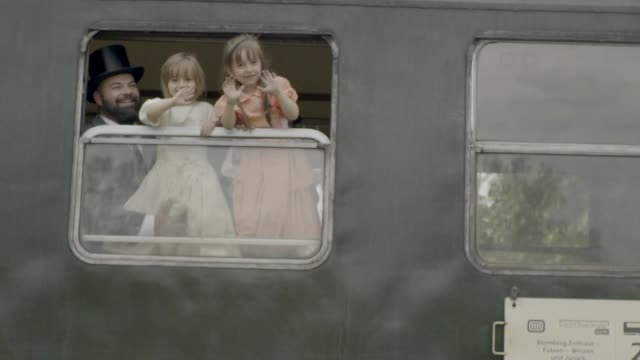 Father and daughters waving out of an old steam train car Victorian family visiting old train station 19th century style stock videos & royalty-free footage