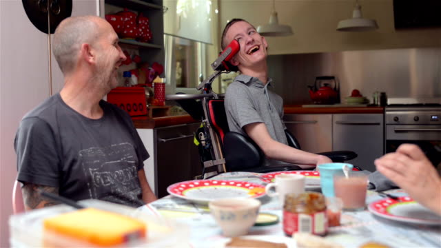 Father and disabled son Full HD color footage of a real life male Cerebral Palsy having lunch with his mother and father. disability stock videos & royalty-free footage