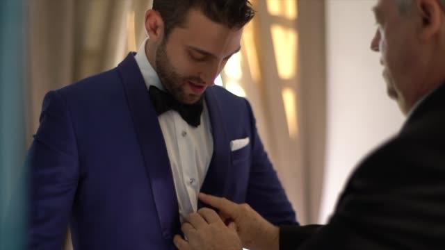 vídeos y material grabado en eventos de stock de padre y novio vistiéndose para la boda - novio relación humana