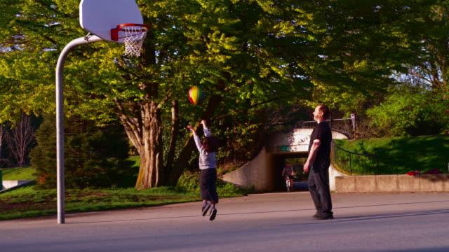 Father and his 7-years-old son playing basketball in the Stanley Park, Vancouver, Canada