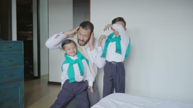 vater und seine kinder fertig, um sich darauf vorzubereiten, das haus zu verlassen - lateinische schrift stock-videos und b-roll-filmmaterial