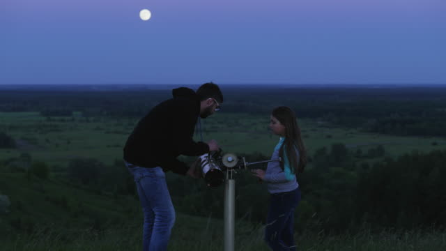 father and his daughter look through a telescope at the moon - lega sportiva amatoriale video stock e b–roll