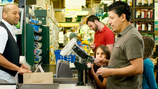 Father and his two daughters go through checkout line video