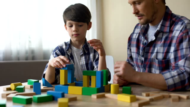father and serious son playing with toy cubes, building house together, leisure - vivere semplicemente video stock e b–roll