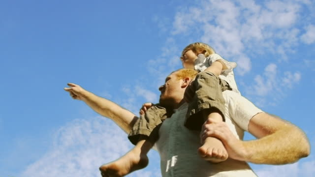 Father and Son 02 A father holding his son on his shoulder in front of an animated sky background pointing stock videos & royalty-free footage