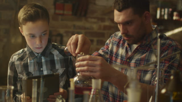 Father and son are making chemistry experiments while checking a tablet computer in a garage at home. video