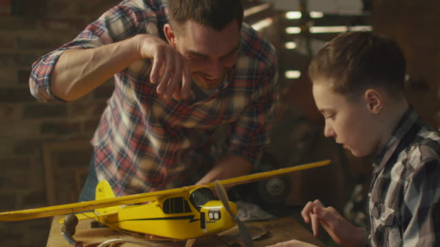 Father and son are modeling a toy airplane in a garage at home.