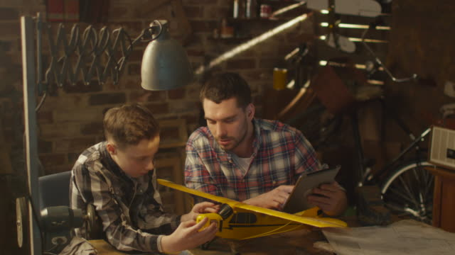 Father and son are modeling a toy airplane while checking instruction on a tablet computer in a garage at home.