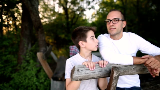 Father and son are resting from walking on a bench in nature video