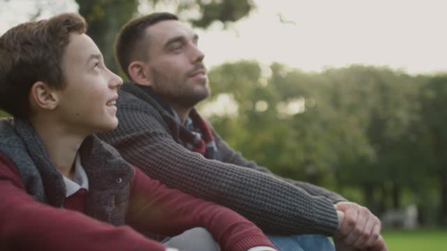 父と息子が公園で座っていると話しています。父の抱擁息子。 - 息子点の映像素材/bロール