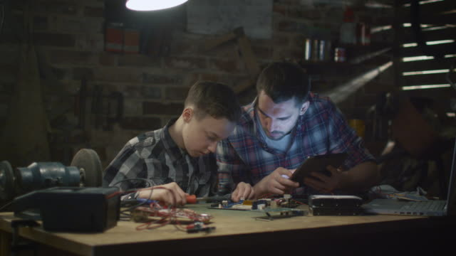 Father and son are soldering a circuit board in a garage at home. video