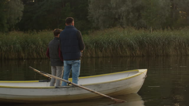 Father and Son are Standing in the Boat and Fishing. video