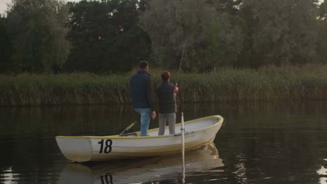 Father and Son are Standing in the Boat while Fishing. Son Swings Fishing Rod. Father Encourages Son. video
