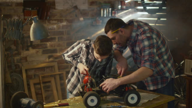 father and son are working on a radio control toy car in a garage at home. - giocattolo video stock e b–roll