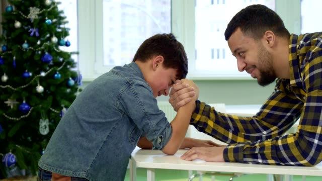 Father and son armwrestle on the table video