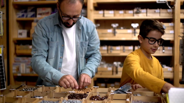 Father and son arrangement of product in store video