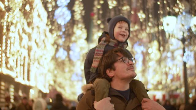 vídeos y material grabado en eventos de stock de padre e hijo en un mercado navideño - foto natural