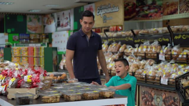 vídeos y material grabado en eventos de stock de padre e hijo en la sección de panadería de un supermercado e hijo pidiéndole a papá que compre galletas - galleta dulces