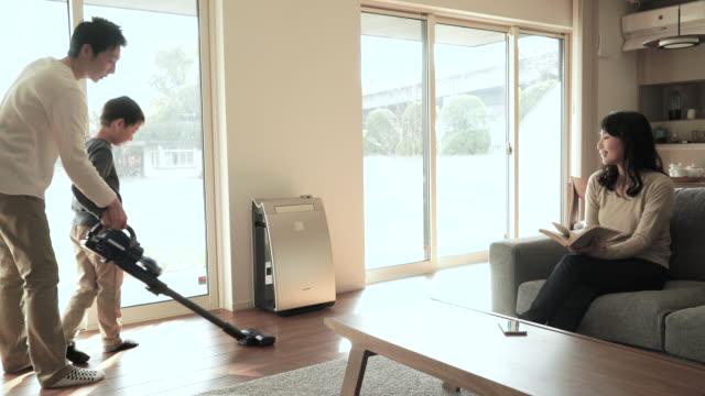 Vater und Sohn Reinigung mit Staubsauger im Wohnzimmer – Video
