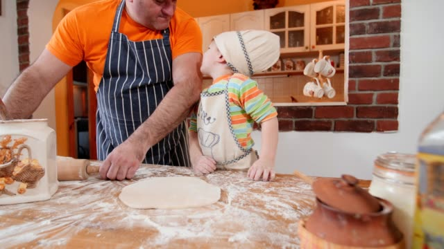 vídeos de stock e filmes b-roll de father and son cooking in the kitchen. - baking bread at home