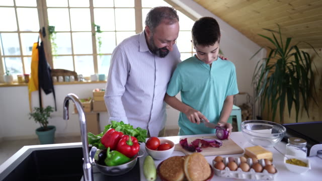 Father and son cutting onion in the kitchen