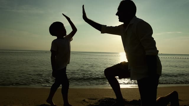 Father and Son doing high five on the beach at sunrise, They spend quality family time together.