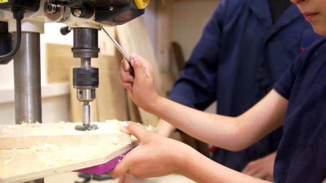 stockvideo's en b-roll-footage met vader en zoon boren de houten plank met behulp van schrijnwerkerij machine in houtklas - elektrisch gereedschap