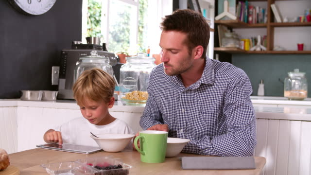 Father And Son Eating Breakfast Whilst Using Digital Tablets video