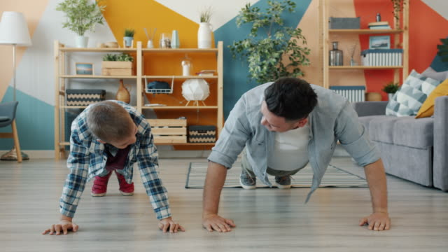 Father and son exercising together doing push-ups indoors in apartment video