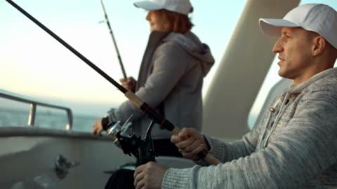 vidéos et rushes de hd: père et fils de pêche de la poupe - transport nautique