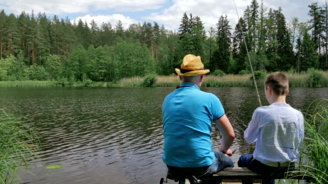 father and son fishing on the bench of the river - bench stock videos & royalty-free footage