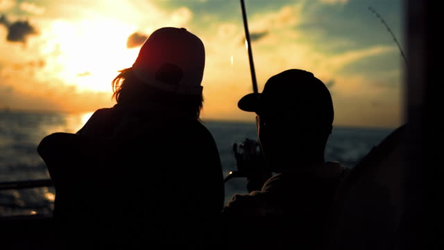 hd: father and son fishing on the boat at sunset - segling bildbanksvideor och videomaterial från bakom kulisserna