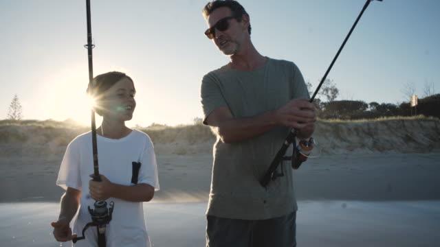 stockvideo's en b-roll-footage met vader en zoon samen vissen op het strand - teenager animal