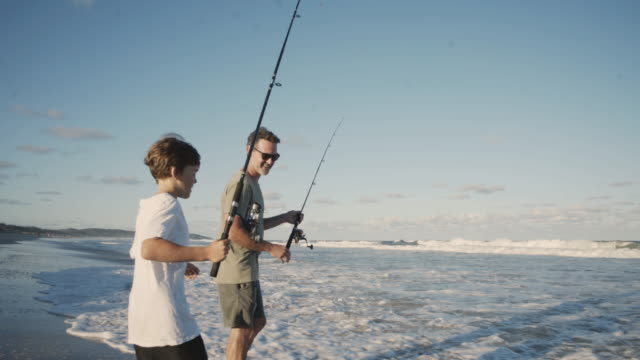 father and son fishing together at the beach - fishing stock videos and b-roll footage