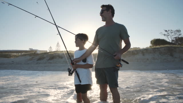 Father and son fishing together at the beach