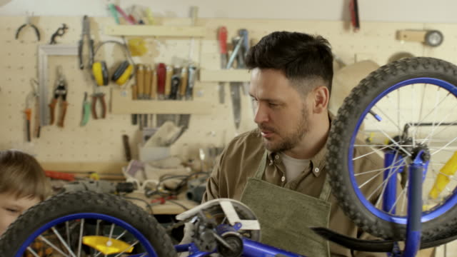 Father and Son Fixing Bicycle in Garage PAN of bearded father in apron fastening nuts on front wheel of bicycle standing upside down on workbench in garage, then talking and helping little son tightening bolts on rear wheel workbench stock videos & royalty-free footage