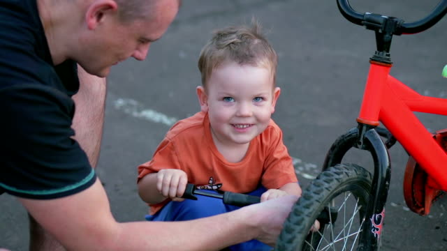 Father and son fixing bicycle tire on sidewalk