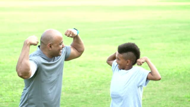 father and son flexing muscles - stalowy filmów i materiałów b-roll