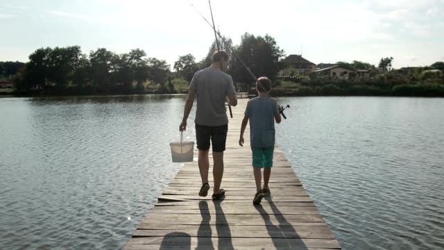 vídeos de stock e filmes b-roll de father and son going fishing with rods on lake - docas