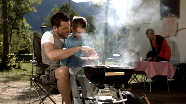 HD DOLLY: Father And Son Grilling Meat On Barbecue video