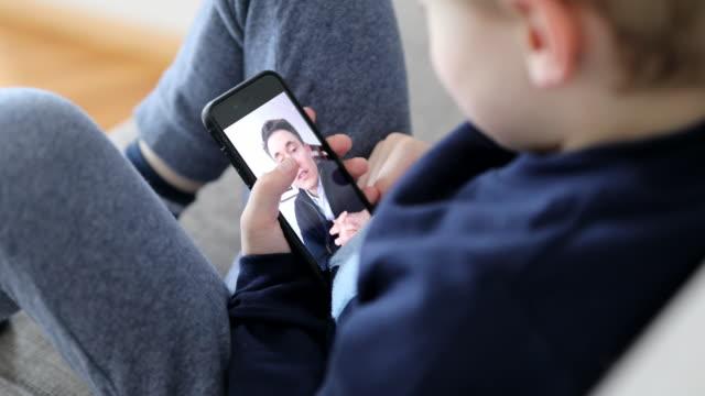 Covid-19ロックダウン隔離中にビデオ通話を行っている父と息子 ビデオ
