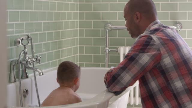 vidéos et rushes de père et fils ayant l'amusement à l'heure de bath ensemble - prendre un bain